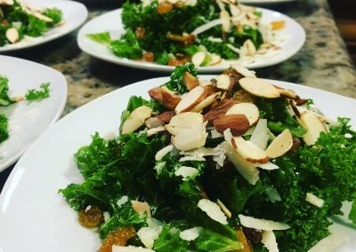 Baby kale and marinated raisins in a white balsamic vinaigrette, with sliced almonds and parm